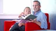Little boy reading with father or grandfather