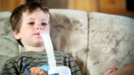A little boy sits on a couch and uses a nebulizer to inhale medicine.