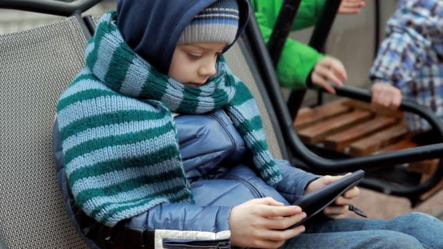 little boy sitting alone on swing with digital tablet