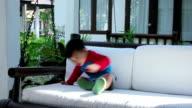 Little boy sitting in swing chair on a balcony
