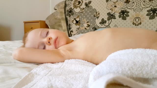 Little boy sleeping on bed