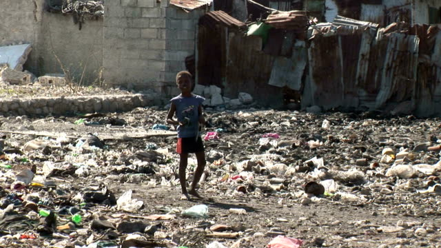 Little boy standing amidst rubble and garbage / people living in refugee camp / woman sweeping garbage out of dirt street Haiti streets after...