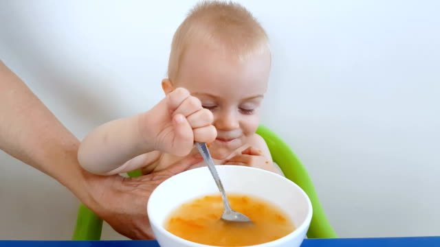 Little boy trying to eat spilling soup on himself