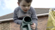 Little Boy Using A Watering Can To Water Seeds