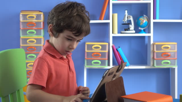 Little Boy Using Digital Tablet In His Room