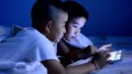 Little boy using tablet under the blanket
