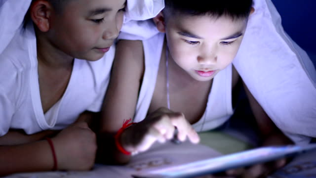 Little boy using tablet under the blanket