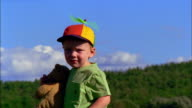 A little boy wearing a propeller hat holds a teddy bear.