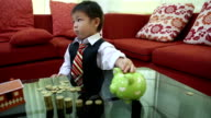 little boy with house model and pile of coins