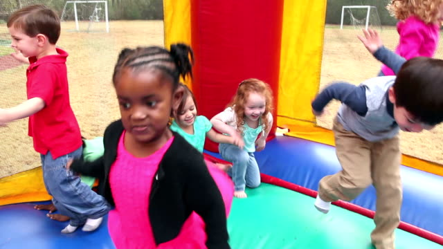 Little boys and girls jumping in bouncy castle
