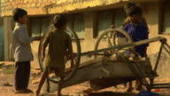 WS Little boys playing with wheels of upturned cart in village, Lalkuan, Uttarakhand, India