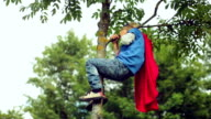Little boy-superman climbs on a tree.