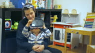 Little child with his mother is using VR glass in his bedroom