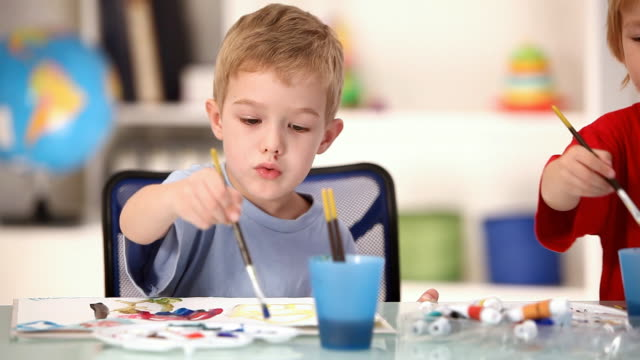 Little children painting in the classroom, camera move, HD video