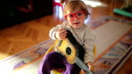 Little cute girl playing toy guitar and singing