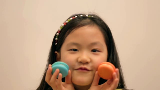 Little East Asian girl playing with macaroon