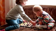 Little girl and her baby sister placing chess pieces