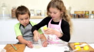 Little girl and her brother baking