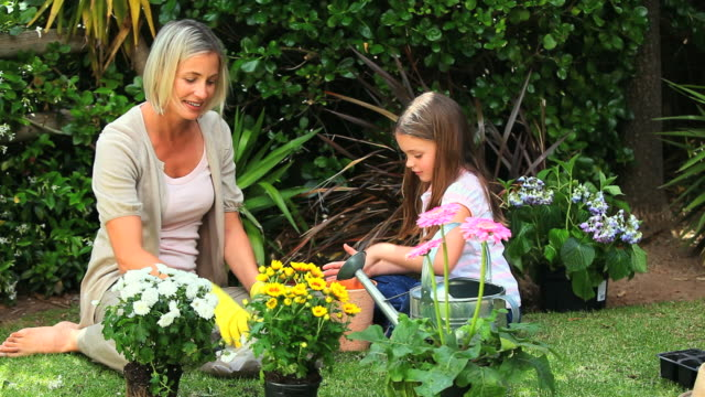 Little girl and mother potting flowers in garden / Cape Town, Western Cape, South Africa