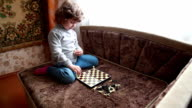 Little girl arranging chess pieces on the chessboard