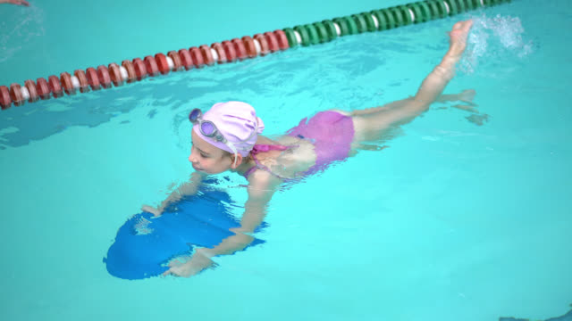 Little girl at the pool learning to swim using a swimming board