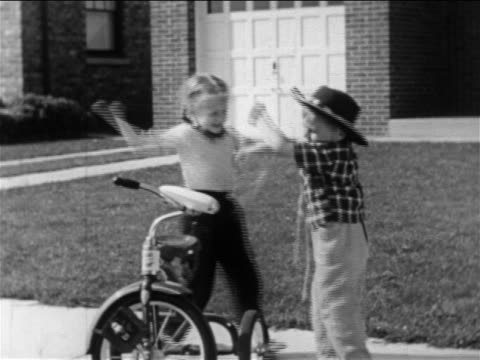 B/W 1950 little girl beating up little boy with cowboy hat by tricycle on sidewalk / educational