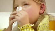 Little girl coughing and cleaning her nose.