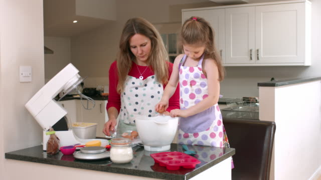 4K: Little Girl Cracking an Egg while Baking with Mummy