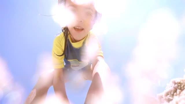Liten flicka gräva upp kameran från Sand på sommaren Resort.