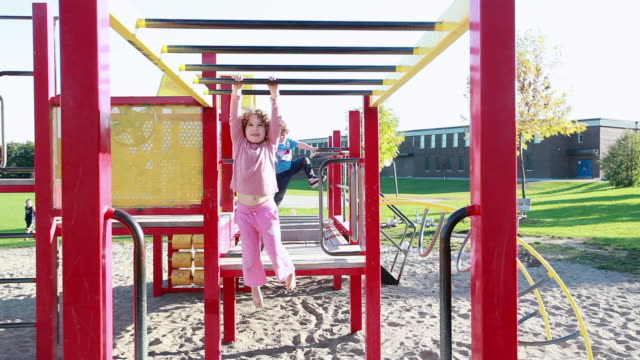 MS Little girl does monkey bars at playground and little boy plays in background / Toronto, Ontario, Canada