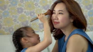 Little girl doing makeup to her mother