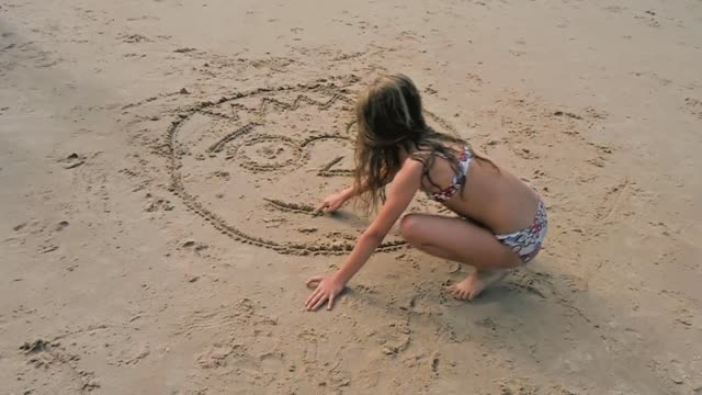Little girl drawing a big smile on the sand of a beach.