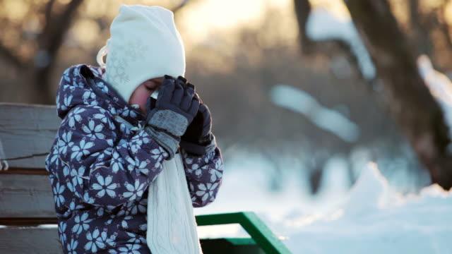 Ragazzina beve del tè caldo nel parco d'inverno