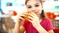 Kleines Mädchen Essen einen burger.