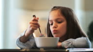 little girl eating cereal and complaining about drinking a healthy green smoothie