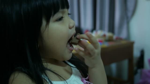 Kleine Mädchen essen Schokolade