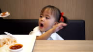 little girl eating fried chicken fried potatoes in fast-food restaurant