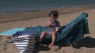 Little Girl eating Yogurt on beach