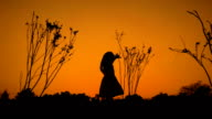 A little girl enjoying at sunset silhouette
