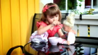 Little girl feeding a doll