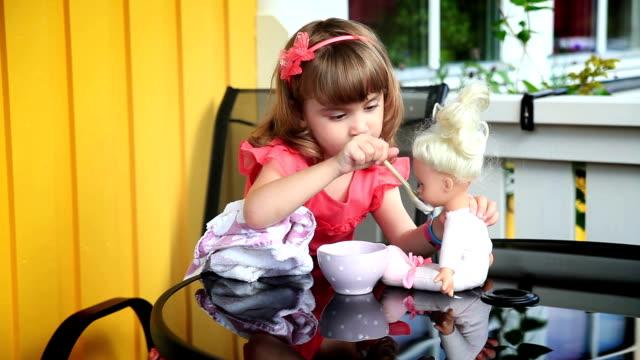 Little girl feeding a doll