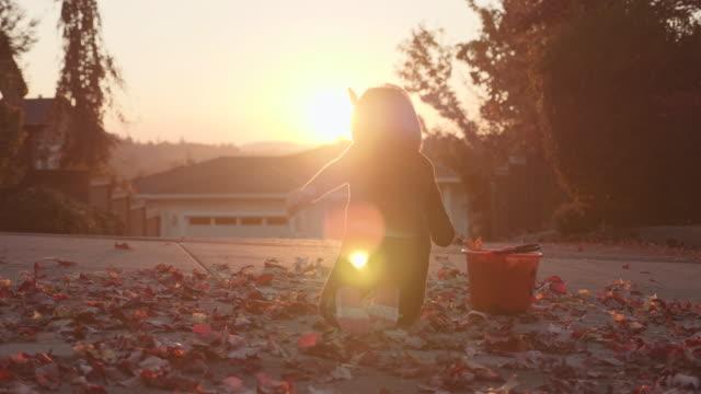 4K UHD: kleine Mädchen sammeln Blätter an einem Herbst-Abend