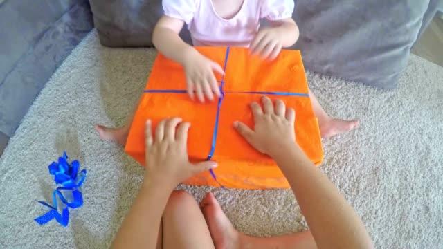 POV kleines Mädchen helfen ältere Schwester öffnen ein Geschenk