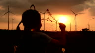 Little girl Hold flowers twilight view wind turbines