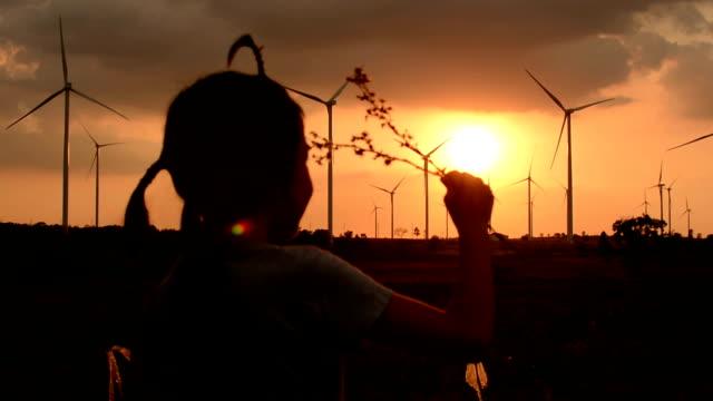 Little girl Hold flowers twilight view wind turbines