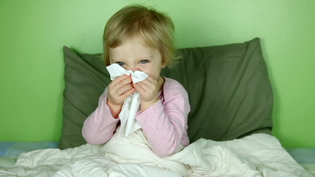 Little girl in bed with runny nose