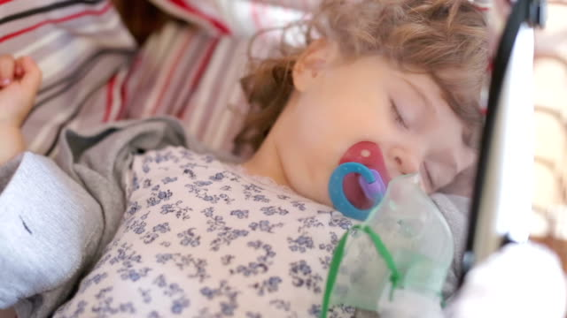 Little girl inhaling medicine