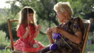 A little girl learning to knit from her grandmother