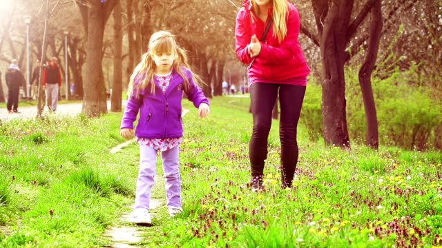 Little girl learning to walk in park with mother