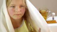 Little girl lying sick in her bed, drinking hot tea.